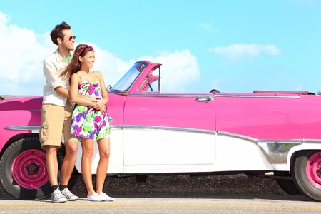 Couple and vintage retro car  Happy smiling young couple standing by pink old vintage car during summer road trip travel in Havana, Cuba  Interracial couple, Asian woman, Caucasian man  photo