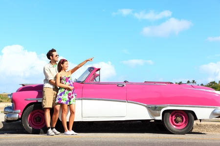 convertible car: Vintage car  Couple pointing looking standing by pink retro vintage car smiling happy  Young couple on summer road trip car holiday in Havana, Cuba  Asian woman, Caucasian man  Stock Photo