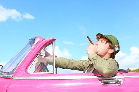 Cuba concept  Vintage car with cigar smoking man with Fidel Castro patrol cap  Funny image cuban conceptual image
