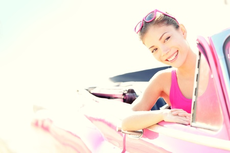 woman driving car: Woman driving vintage retro convertible car in pink  Retro style portrait of young beautiful happy smiling asian woman driver  Stock Photo