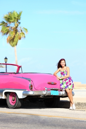 Vintage car and woman standing happy and smiling leaning on pink retro car on the side of the road  Beautiful young multicultural young woman on spring or summer road trip  Havana, Cuba  photo