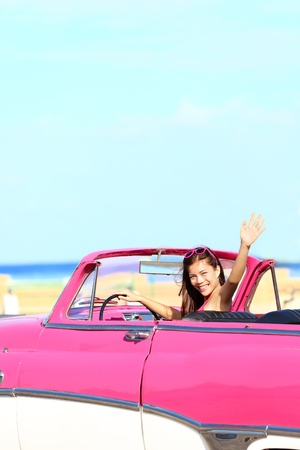 woman driving: Woman driving convertible retro vintage car waving happy during summer drive  Pretty young multicultural Asian   Caucasian young woman driver