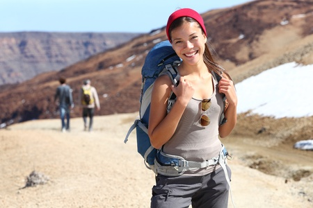 Hiker portrait  Female hiking woman happy and smiling during hike trek on volcano Teide, Tenerife, Canary Islands  Beautiful young mixed race Asian Chinese   Caucasian sporty model joyful