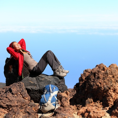 Resting relaxing woman hiker lying down enjoying the sun during hiking travel trek on volcano Teide, Tenerife, Canary Islands, Spain  Beautiful young female hiker
