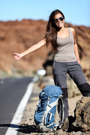 Travel hitchhiker woman happy standing on road side during holiday travel  Beautiful outdoors sporty woman model  photo