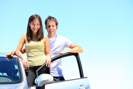 Couple and new car smiling happy standing outside on sunny summer day during road trip travel vacation  Young interracial couple in their twenties, Asian woman, Caucasian man