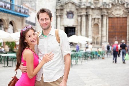 tour guide: Cuba los turistas en La Habana retrato feliz pareja durante el viaje en La Habana, Cuba, mujer asi�tica, hombre de raza cauc�sica sonriendo feliz en la Plaza de la Catedral, Habana Vieja