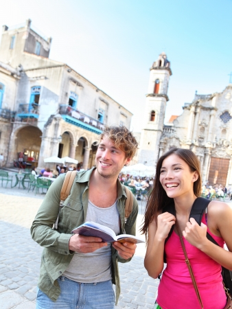 caribbeans: Tourists couple travel having fun smiling happy in Havana, Cuba   Young interracial happy couple on backpacking vacation standing holding reading tourist guide book on Plaza de la Catedral, Old Havana
