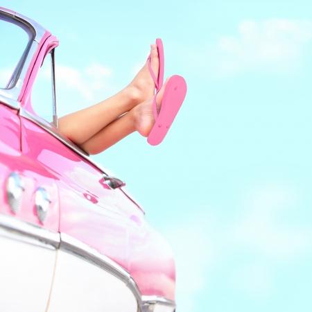 sandalia: Piernas de verano divertidas de coches de �poca se muestra del color de rosa retro vintage Libertad de coches, viajes y vacaciones viaje por carretera de la imagen de estilo de vida con la mujer y el concepto de espacio de la copia en el cielo azul Foto de archivo