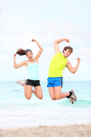 Fitness couple jumping fun on beach during outdoor workout running  Fit young Asian woman fitness model and Caucasian man  photo