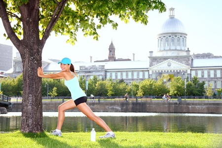 City runner workout woman stretching under tree  Female fitness sport model training outside on sunny summer day in Montreal Old Port, Montreal, Quebec, Canada  Sporty mixed race Asian   Caucasian girl  photo
