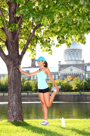 Woman runner in Montreal stretching after jogging workout outdoor on sunny summer day  Montreal Old Port, Montreal, Quebec, Canada  Multiracial Asian   Caucasian female sport fitness model  photo