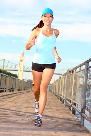 woman running: Woman running  Female runner training outside on sunny summer day in Montreal Old Port, Montreal, Quebec, Canada  Mixed race Asian   Caucasian female fitness sports model outside  Stock Photo