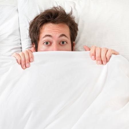 Scared man hiding in bed under the sheets. Funny concept image with young caucasian male model home in bed. Stock Photo - 13093297
