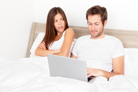 Couple with laptop in bed. Man at computer, woman upset and angry looking at man. Young modern interracial couple in bed. Asian woman, Caucasian man. Funny image. Stock Photo - 13093373