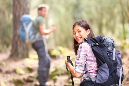 Hikers. Couple hiking in forest. Woman hiker smiling happy at camera walking with hiking poles. Young man in background.