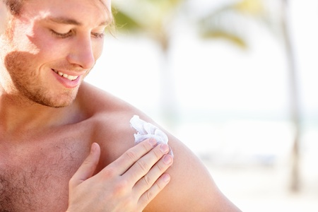 sunscreen: Solar cream  sunscreen. Man putting sunblock sun screen cream on the beach under the sun during vacation on travel resort. Young caucasian male model.
