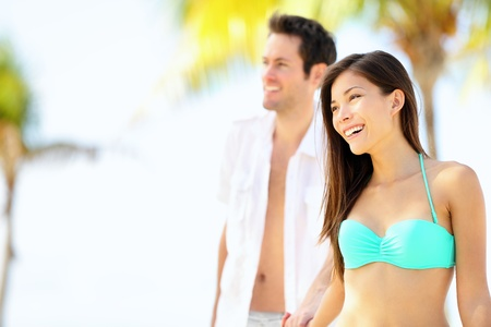 Happy couple on beach vacation travel walking under the sun on sunny summer day. Young beautiful interracial couple, Asian woman, Caucasian man. Stock Photo - 13093367