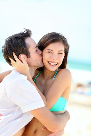 novios besandose: Feliz pareja bes�ndose y abraz�ndose en la felicidad alegre que muestra el amor durante las vacaciones de verano, playa. Hermosa joven pareja interracial, mujer asi�tica, al aire libre del hombre cauc�sico.
