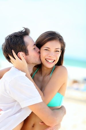 young couple hugging kissing: Happy couple kissing and embracing in joyful happiness showing love during summer beach vacation. Beautiful young interracial couple, Asian woman, Caucasian man outdoors.