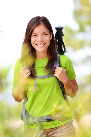 only young women: Hiker portrait - hiking woman standing smiling happy in forest clearing. Beautiful sporty healthy lifestyle image of young fresh multiracial hiker woman on trek. Stock Photo