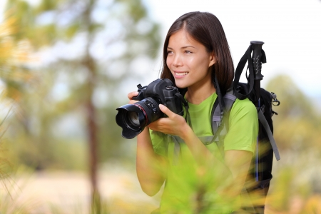 photographing: Nature travel photographer woman taking pictures in forest during hiking trip. Beautiful happy smiling young woman holding professional SLR camera. Mixed race Chinese Asian  Caucasian girl photographing