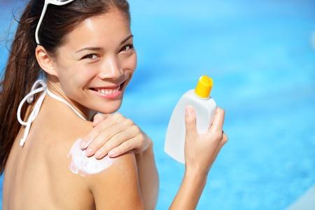 Protezione solare / sunblock. Donna, mettere la crema solare sulle spalle sorridente all'aperto felice nella piscina sotto il sole sul bel giorno d'estate. Razza mista ragazza asiatica / caucasica. Archivio Fotografico