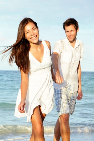 woman beach dress: Beach couple happy holding hands. Young beautiful couple in love walking on beach at sunset. Asian woman, Caucasian man.
