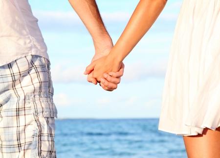 Tomados de la mano pareja en la playa. Imagen romántica del concepto de amor y felicidad con la feliz pareja joven. De cerca.