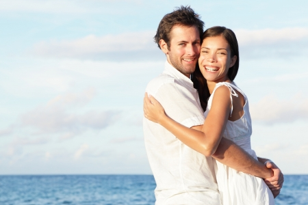 Happy young couple on beach in love embracing and hugging smiling joyful. Interracial young couple, Asian woman, Caucasian man. photo