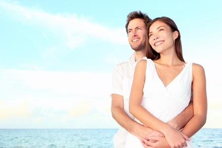 multicultureel: Gelukkig strand paar portret van mooie jonge romantische interracial paar lachende gelukkige omarmen op het strand tijdens de zomer vakantie. Blanke man, Aziatische vrouw. Stockfoto