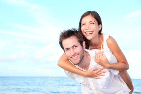 Happy beach couple doing piggyback having summer vacation fun. Young interracial couple, Asian woman, Caucasian man. photo