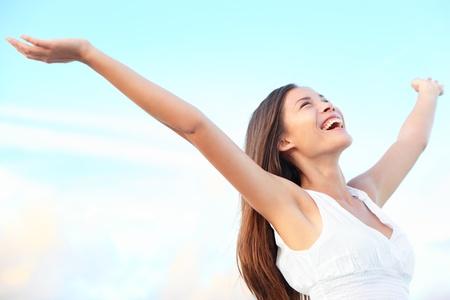 rozradostněný: Štěstí blaženosti svobody koncept. Žena usměvavé radostný s rukama nahoře tančí na pláži v létě během svátků jezdit. Krásná mladá veselá Smíšené rasy asijské čínská  Kavkazská ženského modelu venkovní.