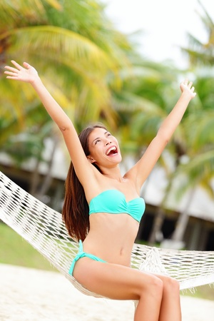 Vacation woman on beach happy and joyful with arms raised sitting in hammock. Beautiful young bikini model in summer holidays resort. Mixed race Caucasian / Chinese Asian woman. photo