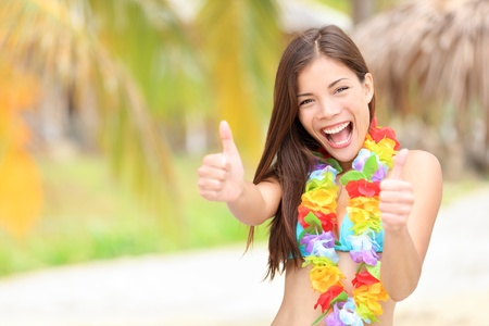 Vacation summer fun woman showing thumbs up smiling happy in joyful bliss. Pretty mixed race Asian / Caucasian female bikini model cheerful on beach. photo