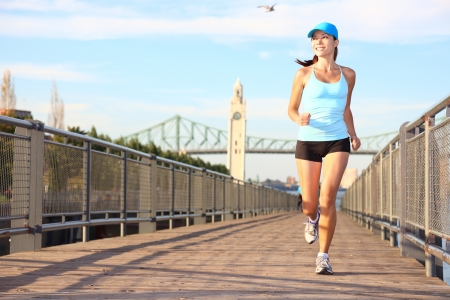 montreal: Running in city. Woman runner sport fitness model working out jogging smiling happy in Old Port of Montreal, Quebec, Canada. Beautiful young multiracial female runner. Stock Photo
