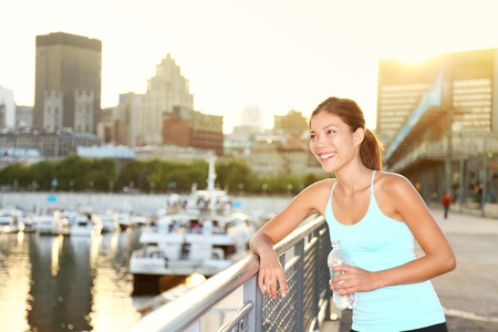 Woman city runner resting after running workout. Female fitness model smiling happy drinking water enjoying a break. Beautiful fit mixed race Asian Chinese and Caucasian woman outdoors. photo