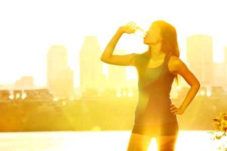sediento: Corredor de verano mujer de agua potable bajo el sol en el día cálido y soleado en el parque de la ciudad con el paisaje urbano de rascacielos en el fondo. Hermosa joven corredor fitness femenino relajarse después de hacer ejercicios al aire libre en Montreal, Quebec, Canadá. Corredor mujer multirracial. Foto de archivo