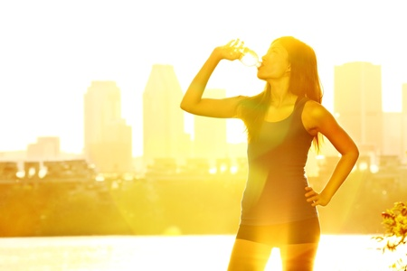backlit: Summer runner woman drinking water in sunshine on warm sunny day in city park with cityscape skyline in background. Beautiful young female fitness runner relaxing after outdoor workout in Montreal, Quebec, Canada. Multiracial woman jogger.