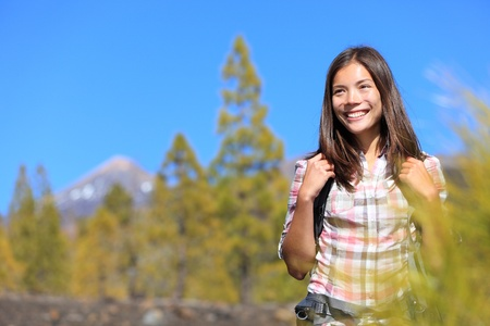 Hiker. Hiking woman portrait of happy female outdoors person during hike in forest on volcano Teide, Tenerife, Canary Islands, Spain, Young mixed race Asian Chinese  Caucasian girl. photo