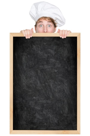 blackboard background: Funny chef showing blank empty blackboard menu sign for restaurant menu or recipe. Man chef cook or baker hiding behind chalkboard peeking over funny. Isolated on white background.
