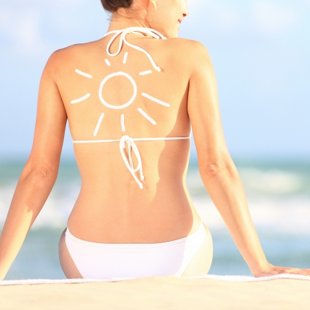 sunblock: Sunscreen   sun tan lotion sun drawing on woman back  Girl in bikini sitting on beach in sunlight