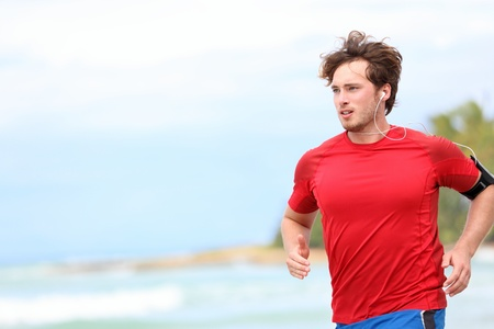 joggers: Man jogging on beach  Male runner running listening to music on mp3 player or smart phone  Young caucasian male fitness sport model in red t-shirt  Stock Photo