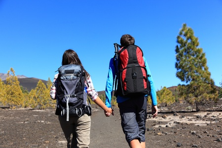 backpacking: Hiking couple holding hands walking on volcano landscape on Teide, Tenerife, Canary Islands, Spain