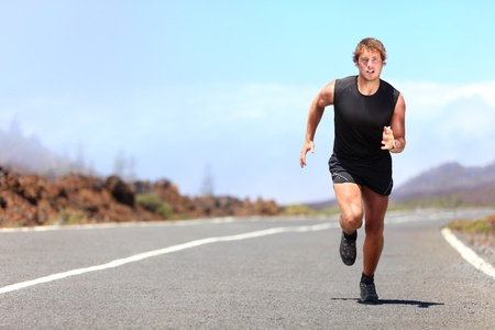 Man running   sprinting on road in mountains  Fit male fitness runner during outdoor workout  Young caucasian man  Stock Photo