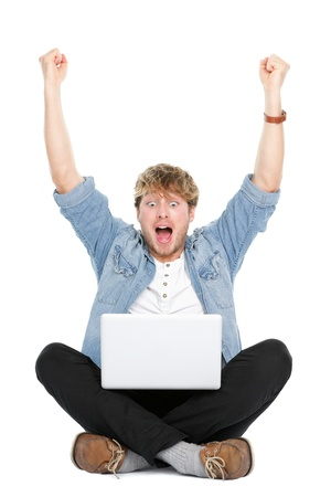 excited: Man cheering with laptop computer and arms raised winning happy.  Young caucasian male model sitting on floor isolated on white background.