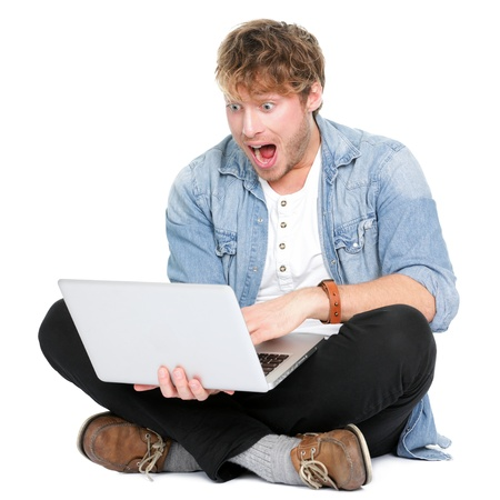 Man surprised with laptop computer looking at screen excited and happy in disbelief. Funny image of young Caucasian male student model sitting on floor isolated on white background. photo