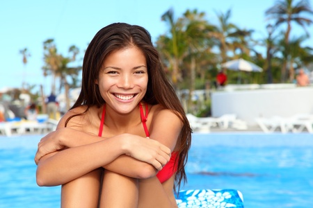 young girl bikini: Vacation girl at pool  Happy portrait of young woman in summer holiday resort  Gorgeous mixed race Asian   Caucasian female model in bikini