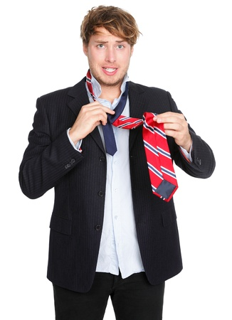 Man tying a tie  Funny man unable to tie his tie trying hard  Young male businessman in suit getting dressed isolated on white background  photo