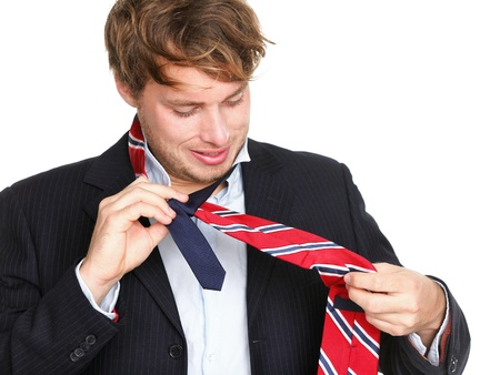 formal dressing: ties - man can not tie his tie  Young professional business man trying tying his tie getting ready isolated on white background  Funny young caucasian business man model